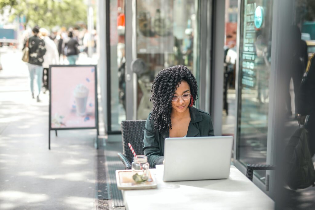 A woman sitting at a computer emailing blog owners about guest blogging opportunities.